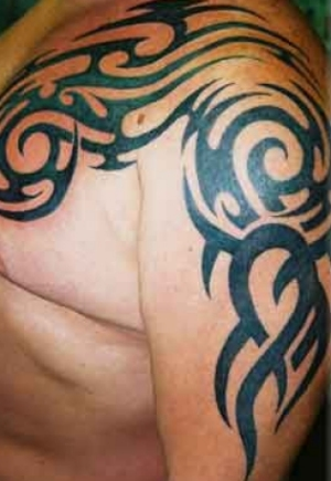 Photo of an arm and chest tribal tattoo.
